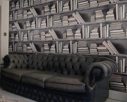 papel-pintado-con-libros-de-yb-con-chester-de-cuero-negro-y-capitone-y-alfombra-de-vaca