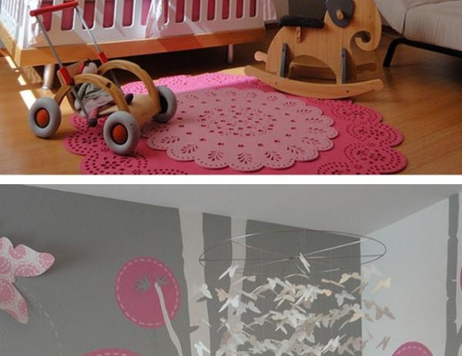 habitación para recién nacido en gris y rosa, con guirnalda de mariposas y cuna blanca, juguetes de madera alfombras rosas